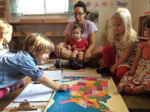 Two 2-year olds intently observing two 4-year olds working with a map.