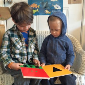 This two year old has a mentor! In this case, one of our 5-year olds is teaching him shapes and modeling the benefits of reading.