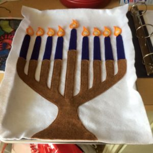 In this material, students are asked to button the flames onto the menorah.